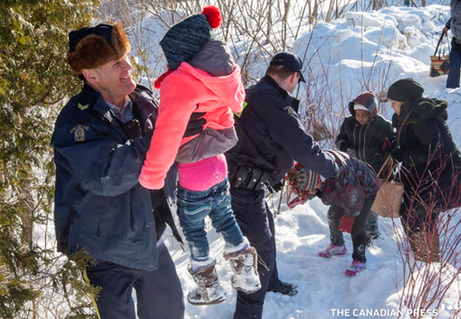 Canadian Mounties greeting refugees from Somalia who walked across the border into Canada.  -Paul Chiasson photo