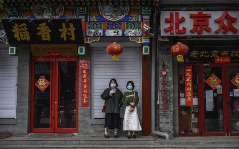 Chinese women wear protective masks as they stand outside closed shops and restaurants near the Forbidden City in Beijing, China on April 19, 2020. (Kevin Frayer:Getty Images