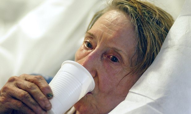 elderly woman who wished to remain unidentified drinks after she was brought by firefighters to the Saint Antoine hospital in Paris during a 2003 heatwave. - Franck Prevel:AP
