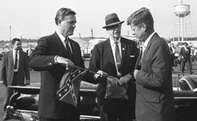 "Handing-JFK-""a-political-football""."
