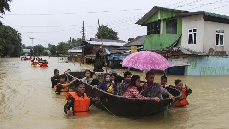 Members of the Myanmar Rescue Team carry residents in a boat to travel along a flooded road in Bago -Myo Kyaw Soe:AP