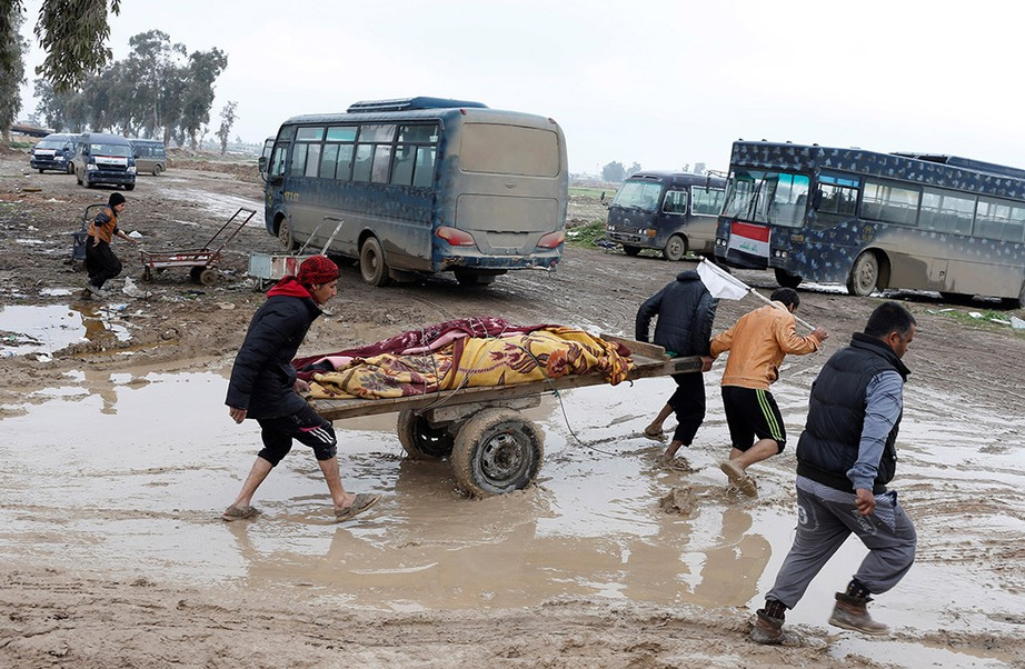 Relatives carry corpses of civilians killed in air strike. -Youssef Boudlal Reuters