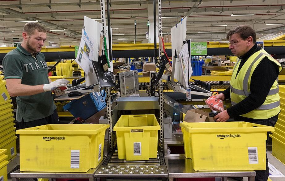 Workers process arriving merchandise in Amazon logistics center DUS2, a 110,000 sq. meters plant established in 2011, in Rheinberg, Germany, December 2, 2014. HORACIO VILLALOBOS : CORBIS VIA GETTY IMAGES