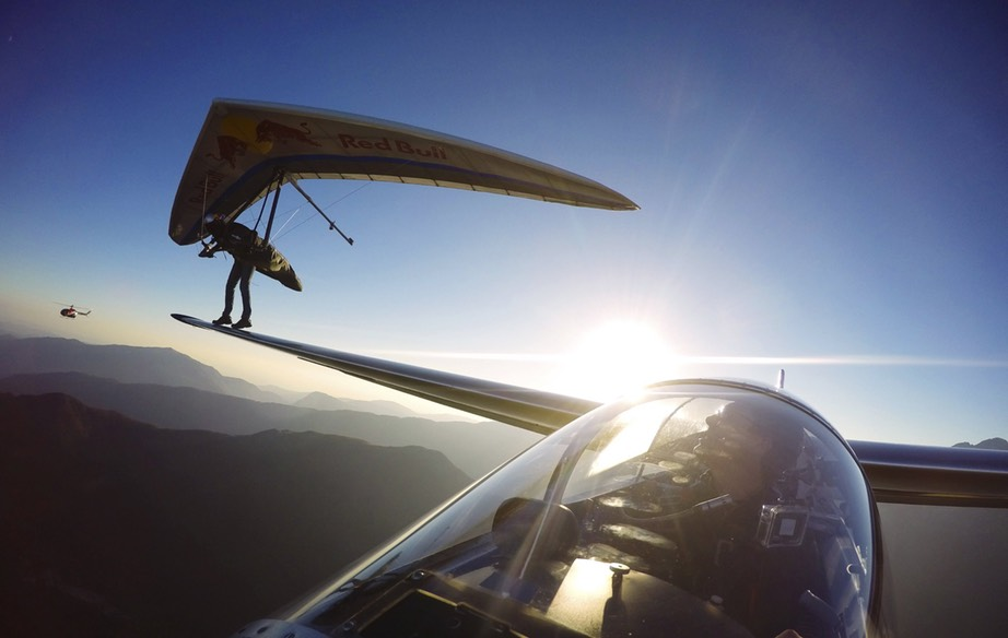 World class hang-glider pilot Matjaž Klemenčič successfully executes a touch-and-go landing on the wing of a sail plane flown by Nejc Faganelj as the two soar over the Soča valley in Slovenia.